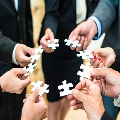 Teamwork – Business people solving a puzzle