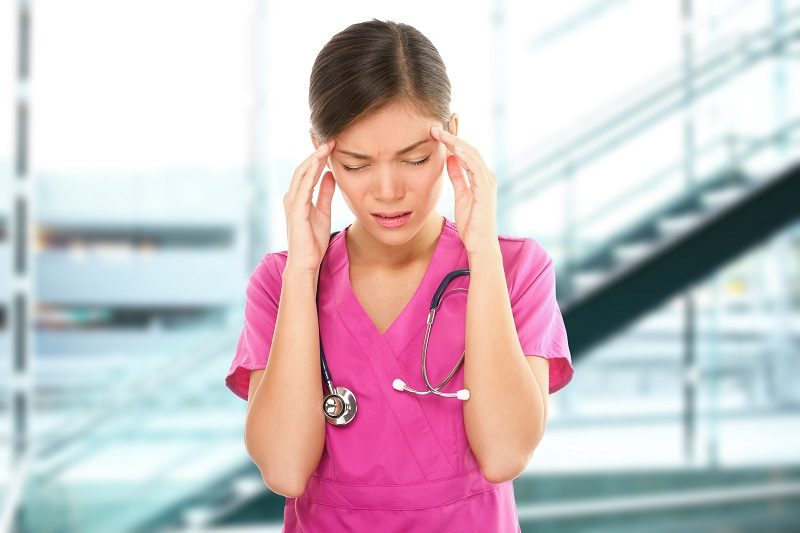 Stressed nurse medical professional with headache