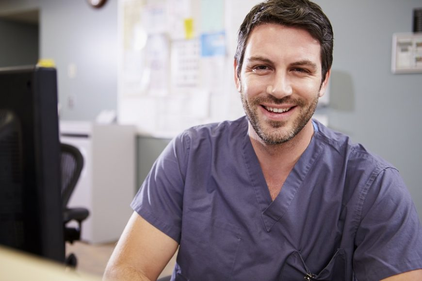 Portrait Of Male Nurse Working At Nurses Station