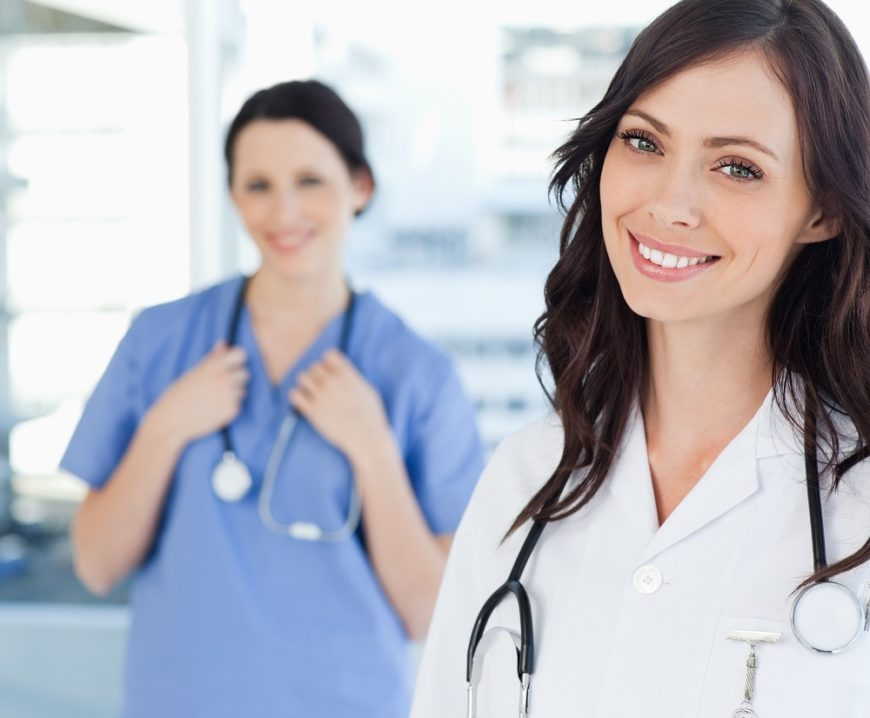 Young smiling nurse standing upright while leaning her head to the side