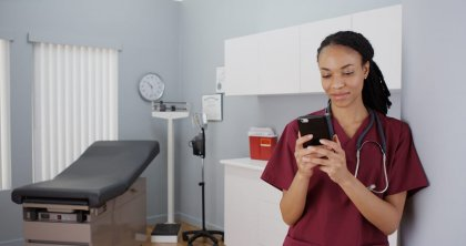 Black woman nurse texting on smartphone
